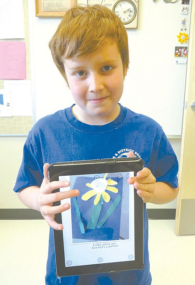 Taelin Campbell displays his Grade 1 art project - a construct of a daffodfil - on his iPad. He took a picture of his creation, then paired it with a poem.