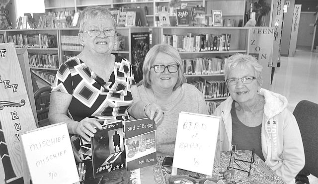 Former local teacher and now author Beth Rowe, left, with teaching colleagues Liz Gardner, centre, and Donna Keay promoted her two books during a book-signing at the High Prairie Municipal Library April 16.