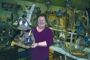 Jacinthe Gervais with her collection of bird houses for sale in the home-based business and crafters show in the curling rink. Gervais makes the bird houses and other items in her garage in Donnelly.