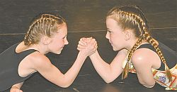 It's not an arm wrestling match but a dance! Aislinn Drefs, left, and Romie Emter battle for supremacy in Master Chef Junior, a novice variety dance choreographed by Zoe Barrons.
