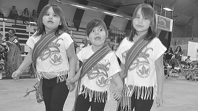 Young girls do some jigging at the powwow. Left-right are Licia Lamouche, 6, Aryiannuh Cardinal, 5, and Kierra Lamouche, 8. Note the traditional Metis sash each is wearing.