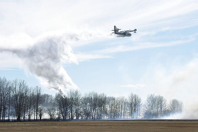 Bombs away! A water bomber douses flames at a grass fire near a residence on Highway 750 on April 28.