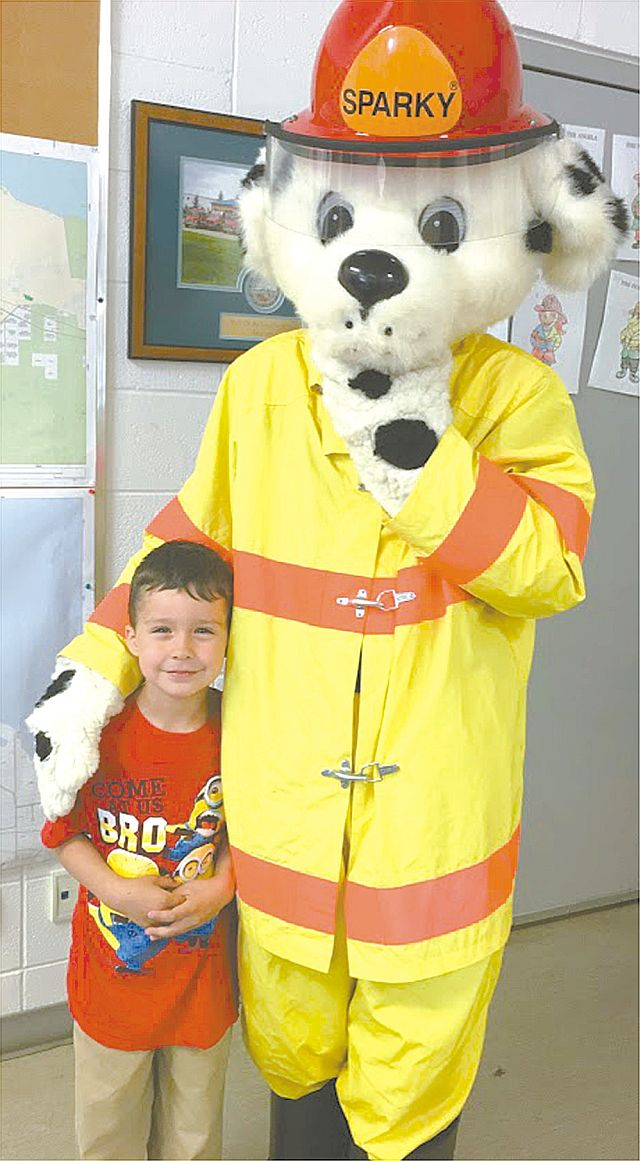 Joussard School student Deigen Willier, left, cuddles up to the ever-popular Sparky the Fire Dog, the fire station mascot.