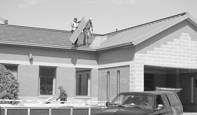Crews work to reroof the Big Lakes County administration building May 25. It's the first step toward major renovations to provide more efficient office space.