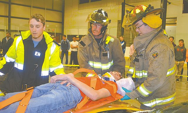 An injured victim played by Zale Zabolotniuk is laid on a spine board. Left-right are Emergency Medical Services EMT Paul Brydson, and High Prairie firefighters Dave Paddon and Capt. Dan Gillmor.