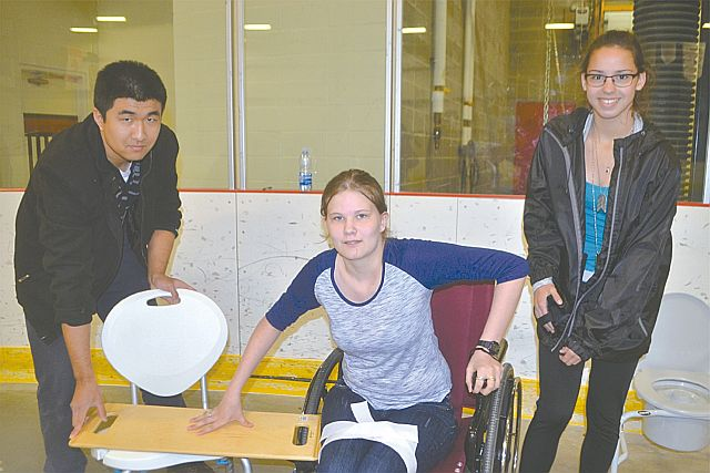Occupational therapist Ron Zhu, left, directs Prairie River Junior High School students Ashley Bell, centre, and Emily Okemow during a mobility challenge.