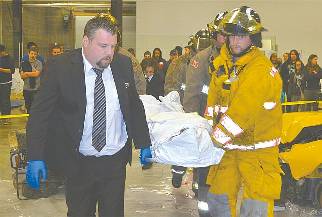 The body of a deceased victim in a body bag is carried into a hearse led by Chris Hicks, left, of the Chapel of Memories, and firefighter David Martinson.