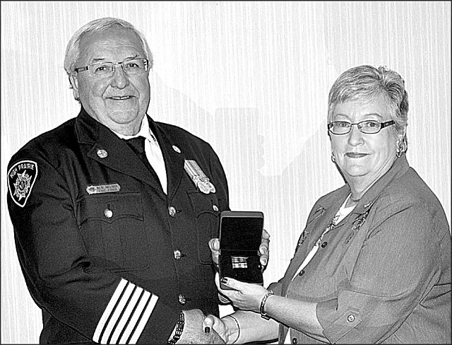 High Prairie fire chief Ken Melnyk, left, receives his 30-year bar from Town of High Prairie Mayor Linda Cox. The bar is part of the Fire Services Exemplary Medal program.