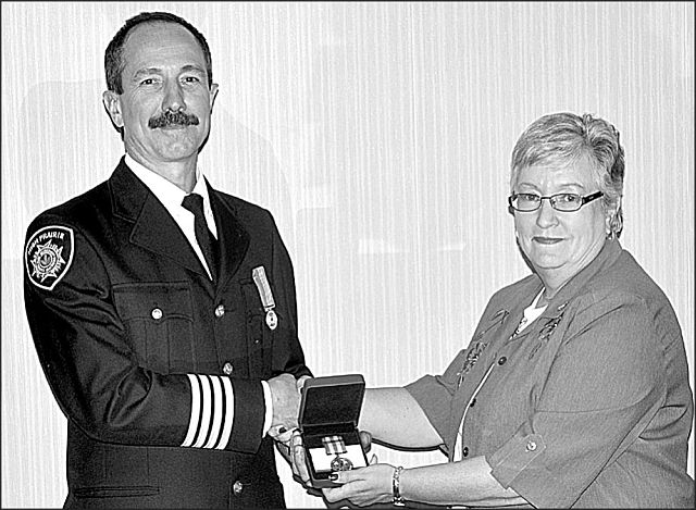 High Prairie deputy fire chief Trevor Cisaroski, left, receives his 20-year pin from Town of High Prairie Mayor Linda Cox. The pin is part of the Fire Services Exemplary Medal program.
