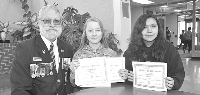 High Prairie Legion president Don Ebbett, left, presents prizes to two St. Andrew's School students: Brooke Buchan, middle, and Krysta Auger. Buchan placed first in Area Intermediate Poems and won $35, and second in District Intermediate Poems and won $55. Auger placed first in Intermediate Colour Poster and won $35.