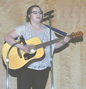 Zoe Blacha sang and played guitar. For her efforts, she placed second in Singles Performance and won $40.
