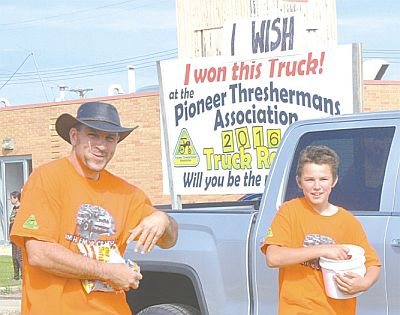 Don't we all wish! Michael Strebchuk, left, and his son, Lukijan, hand out candy courtesy of the Triangle Pioneer Thresherman's Association.
