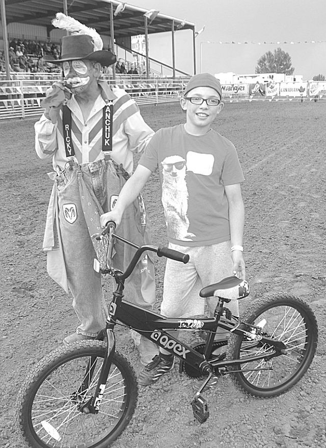 Aiden McLaughlin of Kinuso wins a bicycle as the winner in the calf scramble for children on Aug. 2 as rodeo clown Ricky Ticky Wanchuk leads the fun.