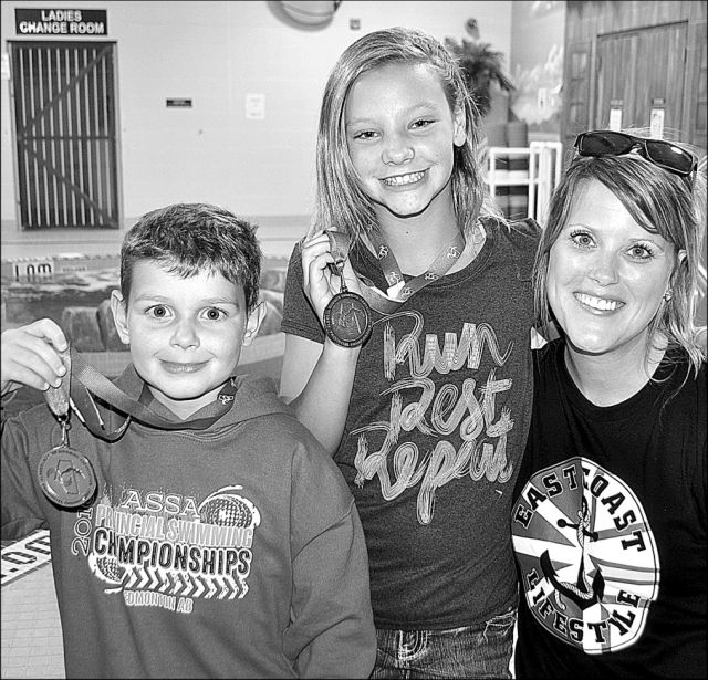 High Prairie Dolphin swimmer Brady Park, left, with his bronze medal and Kirsten Bruder, centre, with her silver medal, they won at the Alberta Summer Swimming Championships. At right is head coach Jenelle Gallivan.