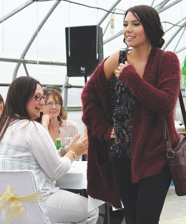 Michelle Dallaire admires Shenay Bellrose' outfit as she walks down the run way in a chunky burgundy cardigan with a weave purse design.