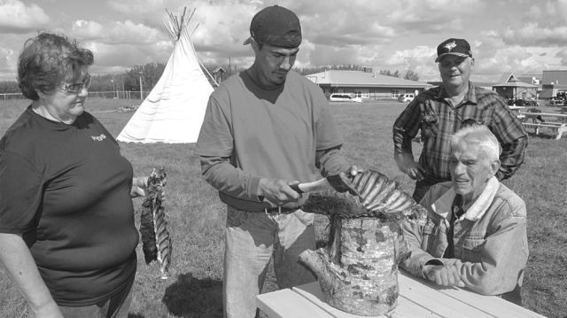 Dwayne Chalifoux cut deer ribs with Ruth Cunningham, left, as Leonard Cunningham, second from right, and Lawrence Villeneuve look on.
