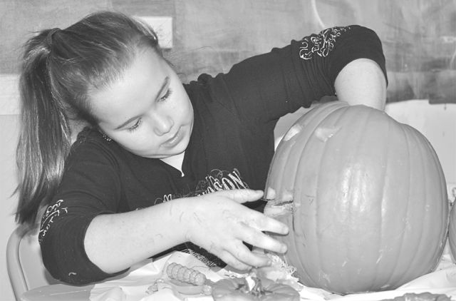 Brooklyn Cox, 10, digs deep to clean out her pumpkin before carving. It was a messy job but a lot of fun at the same time!