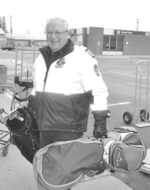 Fire chief Ken Melnyk carries bags of golf clubs into storage.