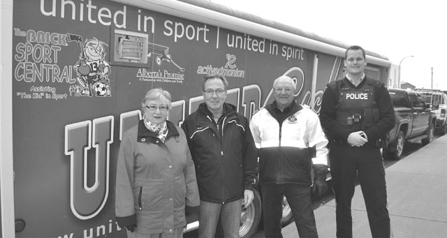 A trailer filled with sports equipment is parked and ready to be unloaded. Left-right are Town of High Prairie Mayor Linda Cox, Sport Central member director Don MacDonald, High Prairie fire chief Ken Melnyk and High Prairie RCMP Cpl. Adam Best.