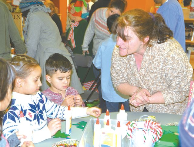 Six-year-old Renah Al-Slaa, left, and three-year-old A.J. Mouallem, centre, receive some helpful tips from High Prairie Municipal Library Board member Yvonne Sanders at a craft table.